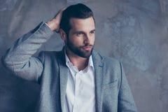 Ο βέβαιος σκεπτικός όμορφος γενειοφόρος νεαρός άνδρας brunette κοιτάζει Στοκ εικόνες με δικαίωμα ελεύθερης χρήσης