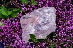 Ο βαθμός πολύτιμων λίθων τραχύς αυξήθηκε χοντρό κομμάτι χαλαζία από τη Μαδαγασκάρη που περιβλήθηκε από το πορφυρό ιώδες λουλούδι στοκ εικόνα με δικαίωμα ελεύθερης χρήσης