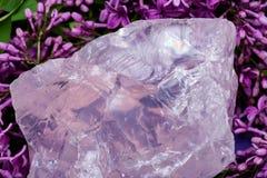 Ο βαθμός πολύτιμων λίθων τραχύς αυξήθηκε χοντρό κομμάτι χαλαζία από τη Μαδαγασκάρη που περιβλήθηκε από το πορφυρό ιώδες λουλούδι στοκ φωτογραφία με δικαίωμα ελεύθερης χρήσης