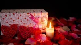 Ο βαλεντίνος μήκους σε πόδηα διακοσμήσεων με τα κιβώτια δώρων, κάψιμο κεριών, και αυξήθηκε πέταλα φιλμ μικρού μήκους