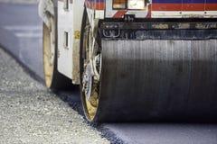 Ο βαρύς συμπιεστής κυλίνδρων δόνησης στο πεζοδρόμιο ασφάλτου λειτουργεί για την κατασκευή δρόμων και εθνικών οδών στοκ φωτογραφία με δικαίωμα ελεύθερης χρήσης