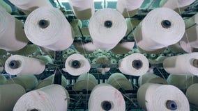 Ο βιομηχανικός εξοπλισμός περιστρέφεται τα κουβάρια με την ίνα σε ένα βιομηχανικό υφαντικό εργοστάσιο απόθεμα βίντεο