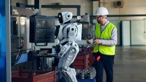 Ο βιομηχανικός εργάτης ελέγχει ένα droid, χρησιμοποιεί μια ταμπλέτα φιλμ μικρού μήκους