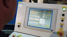 Ο βιομηχανικός εργάτης ελέγχει τη μηχανή, μεγάλος πίνακας ελέγχου μηχανών στο εργοστάσιο φιλμ μικρού μήκους