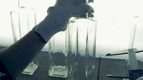 Ο βιομηχανικός εργάτης μετρά το μέγεθος των μπουκαλιών, κλείνει επάνω απόθεμα βίντεο