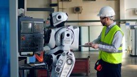 Ο βιομηχανικός εργάτης περπατά και παρατηρεί ένα droid φιλμ μικρού μήκους