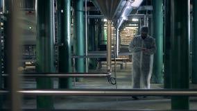 Ο βιομηχανικός εργάτης περπατά κατά μήκος της δυνατότητας οινοπνευματοποιιών με την ταμπλέτα του φιλμ μικρού μήκους