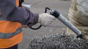 Ο βιομηχανικός εργάτης χρησιμοποιεί τη συσκευή για να ανιχνεύσει το σωρό των ασημένιων σπειρών των ξεσμάτων μετάλλων απόθεμα βίντεο