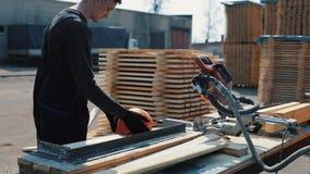 Ο βιομηχανικός νέος εργαζόμενος ξυλουργών παίρνει μια κατασκευή googgles και το κράνος κατασκευής στο χώρο εργασίας του και φεύγε απόθεμα βίντεο