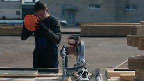 Ο βιομηχανικός νέος εργαζόμενος ξυλουργών φορά μια κατασκευή googgles και έρχεται στην ξύλινη τέμνουσα μηχανή φιλμ μικρού μήκους