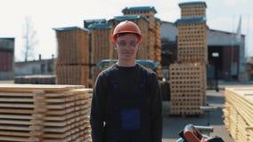 Ο βιομηχανικός νέος εργαζόμενος που φορά το κράνος κατασκευής και παρουσιάζει αντίχειρες Πολλές παλέτες στο υπόβαθρο φιλμ μικρού μήκους