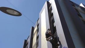 Ο βιομηχανικός ορειβάτης είναι πλύσιμο, καθαρίζοντας την πρόσοψη ενός σύγχρονου κτιρίου γραφείων απόθεμα βίντεο
