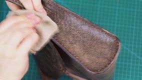 Ο βιοτέχνης γυαλίζει μια άκρη η τσάντα με το κερί απόθεμα βίντεο