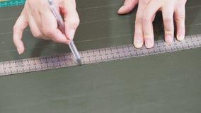Ο βιοτέχνης επισύρει την προσοχή ένα σκίτσο στο πράσινο δέρμα χρησιμοποιώντας ruller και τη μάνδρα απόθεμα βίντεο