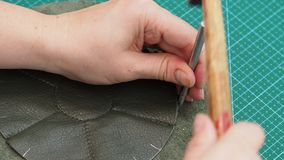 Ο βιοτέχνης κάνει τις τρύπες στη ραμμένη σακούλα από τη διάτρηση και το σφυρί απόθεμα βίντεο