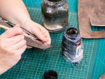 Ο βιοτέχνης λεκιάζει τις άκρες του χαρασμένου στοιχείου δέρματος στοκ εικόνες με δικαίωμα ελεύθερης χρήσης