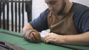Ο βιοτέχνης που εργάζεται στη μαύρη λαβή τσαντών έκανε με το τεχνητό δέρμα στο εργαστήριο φιλμ μικρού μήκους