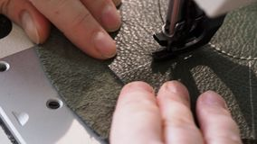 Ο βιοτέχνης ράβει τη σακούλα στη ράβοντας μηχανή κοντά επάνω φιλμ μικρού μήκους