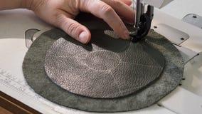 Ο βιοτέχνης ράβει τις λεπτομέρειες της σακούλας στη ράβοντας μηχανή κοντά επάνω απόθεμα βίντεο