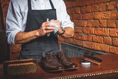 Ο βιοτέχνης σκουπίζει τα χέρια μετά από να γυαλίσει τις μπότες στοκ εικόνα