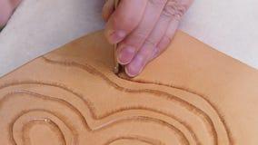 Ο βιοτέχνης σφραγίζει μια διακόσμηση στην επιφάνεια του δέρματος με το εργαλείο σφράγισης Beveler απόθεμα βίντεο