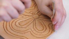 Ο βιοτέχνης σφραγίζει την εικόνα ανακούφισης στο δέρμα με το εργαλείο σφράγισης υποβάθρου απόθεμα βίντεο