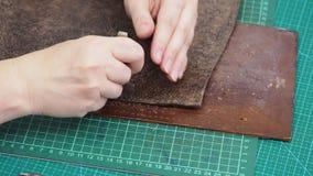 Ο βιοτέχνης τρυπά την άκρη του δέρματος για την τσάντα με διατρητική μηχανή με το ράψιμο της διάτρησης και του σφυριού φιλμ μικρού μήκους
