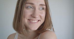 Ο βλαστός κινηματογραφήσεων σε πρώτο πλάνο του νέου αρκετά καυκάσιου θηλυκού με τα δαχτυλίδια τρίχας και ακτινοβολεί makeup γελών φιλμ μικρού μήκους