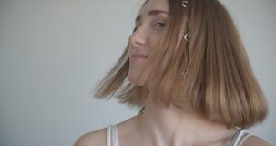 Ο βλαστός κινηματογραφήσεων σε πρώτο πλάνο του νέου αρκετά καυκάσιου θηλυκού με τα δαχτυλίδια τρίχας και ακτινοβολεί makeup χαμογ απόθεμα βίντεο