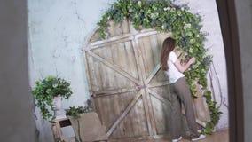 Ο βλαστός στην αντανάκλαση, μοντέρνος ανθοκόμος κοριτσιών διακοσμεί μια όμορφη ξύλινη ζώνη φωτογραφιών με τα λουλούδια απόθεμα βίντεο