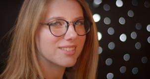 Ο βλαστός σχεδιαγράμματος του ξανθού προτύπου στα γυαλιά με τη φωτεινή σύνθεση χαμογελά prettily στο υπόβαθρο bokeh απόθεμα βίντεο