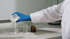 Ο βοηθός εργαστηρίων πλάγιας όψης χύνει την άσπρη πυκνή ουσία στο γυαλί απόθεμα βίντεο