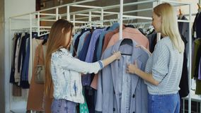 Ο βοηθός καταστημάτων βοηθά τη νέα γυναίκα, φέρνει το παλτό της και λέει για το πρότυπο Ο πελάτης το αγγίζει, σύγκριση απόθεμα βίντεο