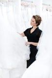 Ο βοηθός καταστημάτων προσπαθεί να υποβάλει την καλύτερη σύσταση φορεμάτων Στοκ Εικόνα