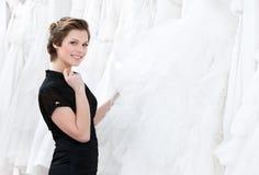 Ο βοηθός καταστημάτων σκέφτεται για τη σύσταση φορεμάτων Στοκ εικόνες με δικαίωμα ελεύθερης χρήσης