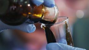 Ο βοηθός χύνει το ακατέργαστο πετρέλαιο από το βολβό στο ποτήρι εργαστηρίων απόθεμα βίντεο
