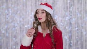 Ο βοηθός Santas με ένα ποτήρι της σαμπάνιας στο χέρι του το πίνει και χαμογελά σημειώσεις μουσικής ανασκόπησης bokeh θεματικές κί απόθεμα βίντεο