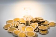 Ο βολβός είναι τοποθετημένος σωρός των νομισμάτων, ο βολβός ανάβει στο σκοτάδι Χρήση εικόνας για την εύρεση μιας εξόδου στο σκοτά στοκ φωτογραφίες