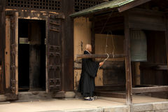Ο βουδιστικός μοναχός χτυπά ένα κουδούνι Στοκ Εικόνες