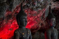 Ο Βούδας, στις αρχαίες σπηλιές, κόκκινο φως λάμπει μέσω της πλάτης στοκ φωτογραφία