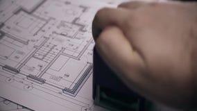 Ο βραχίονας ατόμων ` s βάζει το γραμματόσημο τυπωμένων υλών στο σχέδιο του σπιτιού Θολωμένο σχεδιάγραμμα του σπιτιού στο υπόβαθρο απόθεμα βίντεο