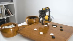 Ο βραχίονας ρομπότ με το παιχνίδι κινέζικα πηγαίνει παιχνίδι Πείραμα με τον ευφυή χειριστή Βιομηχανικό πρότυπο ρομπότ φιλμ μικρού μήκους