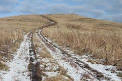 Ο βρώμικος δρόμος φθινοπώρου που πηγαίνει να ολοκληρώσει ενός λόφου φαλακρού Στοκ Εικόνα