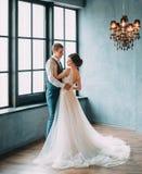 Ο γάμος είναι μια σοβαρή ημέρα Μοντέρνη νέα τοποθέτηση ζευγών ενάντια στο σκηνικό ενός πολυτελούς εσωτερικού Ο νεόνυμφος αγκαλιάζ Στοκ Εικόνες
