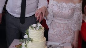 Ο γάμος, η κινηματογράφηση σε πρώτο πλάνο, η νύφη και ο νεόνυμφος κόβουν ένα κέικ φιλμ μικρού μήκους
