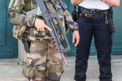 Ο γαλλικός στρατιώτης με ένα αυτόματο ρεύμα ποταμού, ο αστυνομικός στο υπόβαθρο, η ασφάλεια και η έκτακτη ανάγκη δηλώνουν την ένν Στοκ Εικόνες