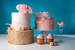 Ο γαμήλιος πίνακας πολυτέλειας με ένα όμορφο ρόδινο κέικ που διακοσμήθηκε με το ροζ μαστίχας αυξήθηκε και χρυσός σε ένα μπλε υπόβ Στοκ εικόνες με δικαίωμα ελεύθερης χρήσης