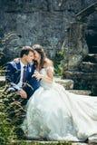 Ο γαμήλιος υπαίθριος πυροβολισμός του όμορφου χαμόγελου τα χέρια και η συνεδρίαση εκμετάλλευσης ζευγών στα παλαιά σκαλοπάτια κάστ Στοκ εικόνα με δικαίωμα ελεύθερης χρήσης