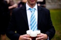 Ο γαμήλιος φιλοξενούμενος φέρνει την μπύρα στοκ εικόνα