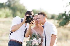 Ο γαμήλιος φωτογράφος παίρνει τις εικόνες της νύφης και του νεόνυμφου στοκ φωτογραφία